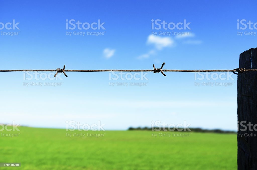 Beautiful countryside cut off by barbed wire fence stock photo