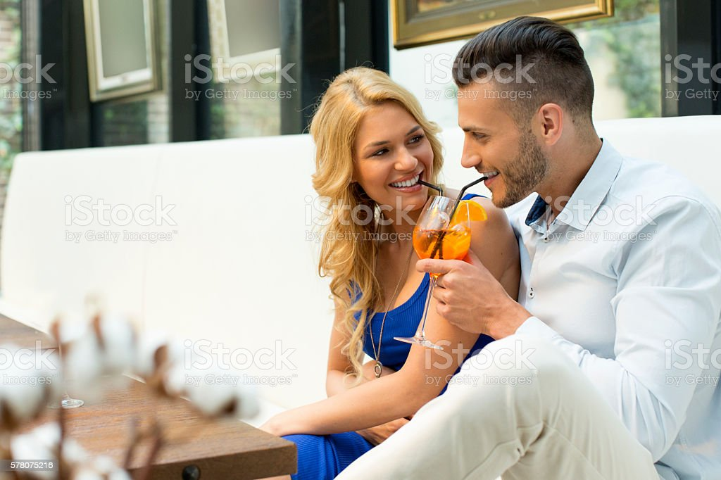 Beautiful couple at the bar sharing a cocktail stock photo