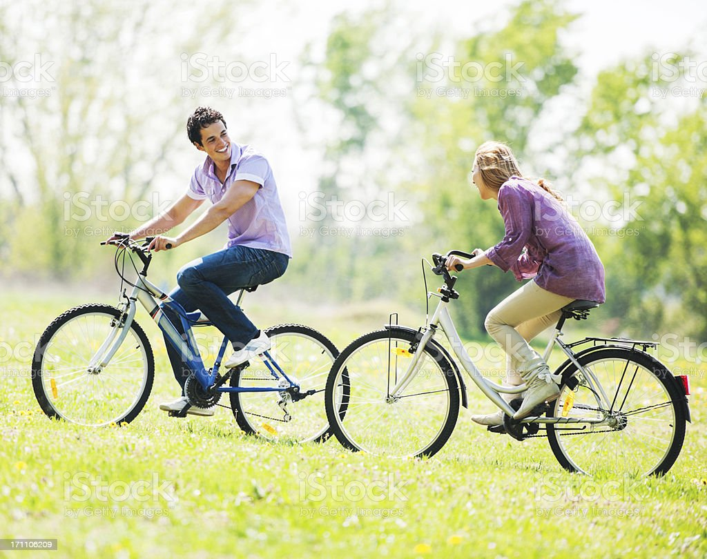 Beautiful couple cycling in the field. royalty-free stock photo