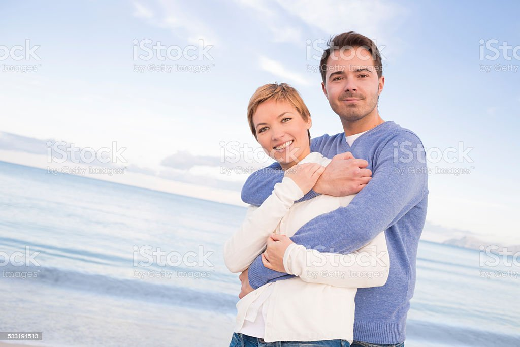 beautiful couple embracing on the beach stock photo