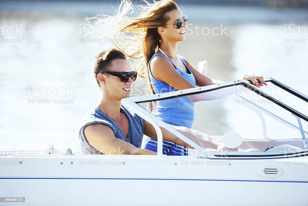Beautiful couple enjoying in a speedboat ride. stock photo