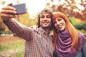 Beautiful couple in park taking selfie for social media