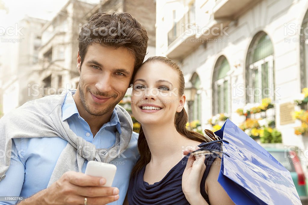 Beautiful couple looking at mobile phone royalty-free stock photo