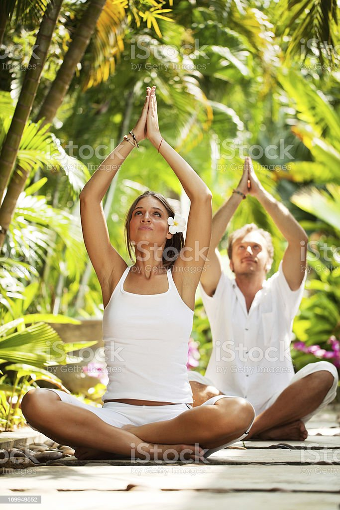 Beautiful couple meditating in a tropical resort. royalty-free stock photo