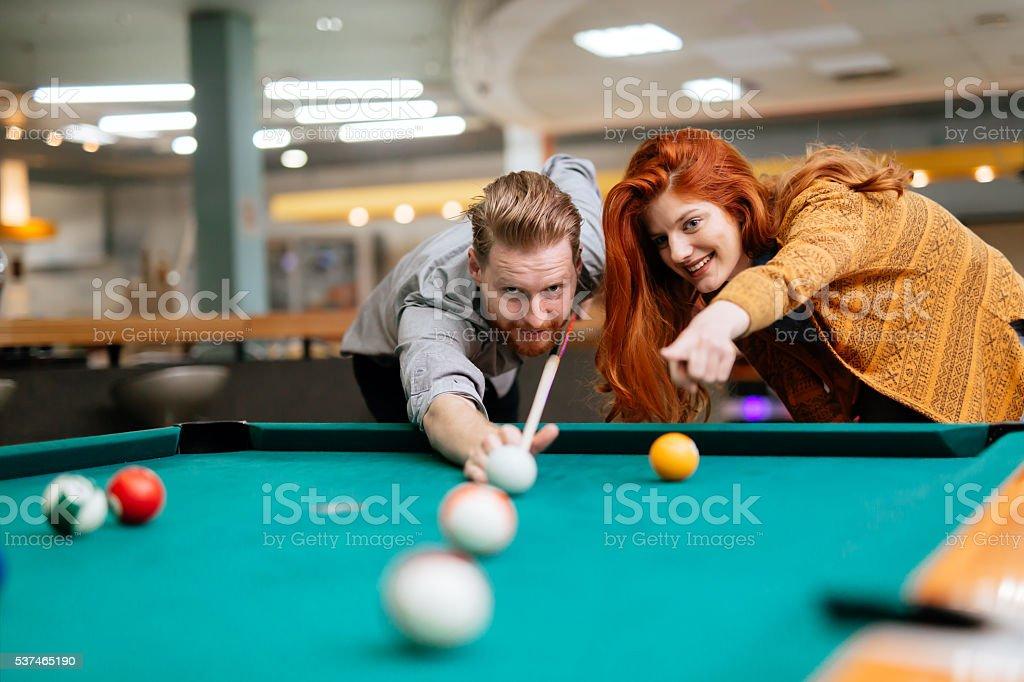 Beautiful couple playing billiards stock photo