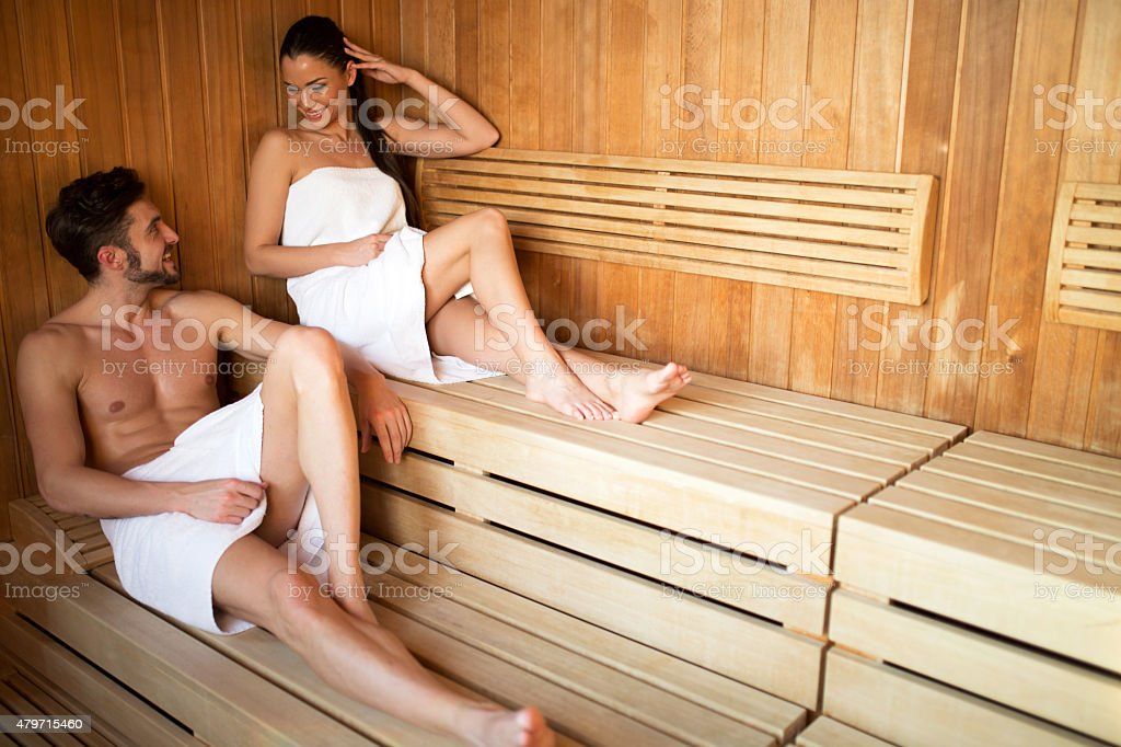 Beautiful couple relaxing in a sauna with towel covering stock photo