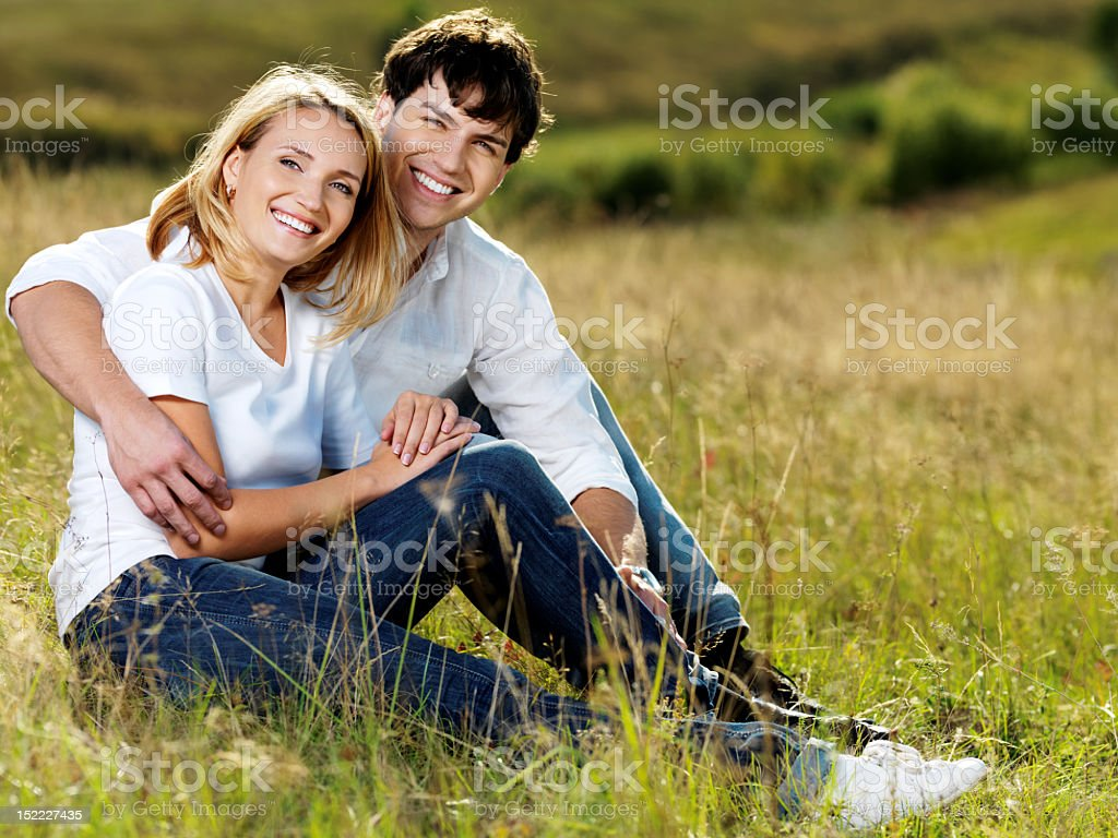 beautiful couple sitting in meadow royalty-free stock photo