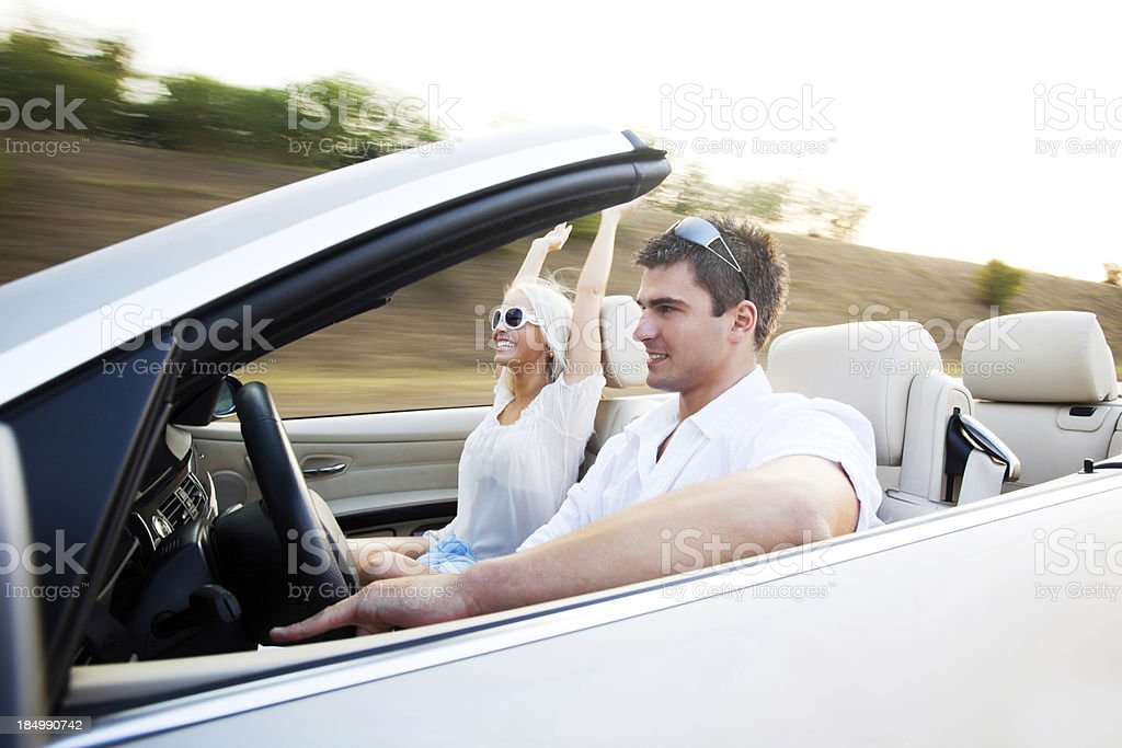 Beautiful couple sitting in their Convertible car. stock photo