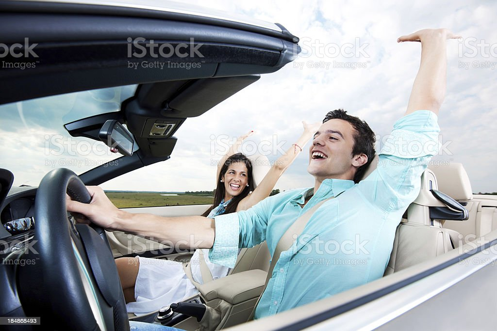 Beautiful couple sitting in their Convertible car with raised hands. royalty-free stock photo