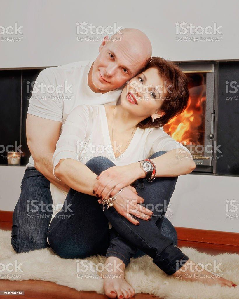 Beautiful couple sitting on fur carpet near fireplace stock photo
