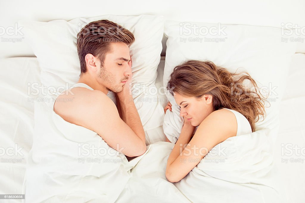Beautiful couple sleeping together in bedroom stock photo