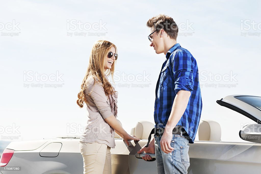 Beautiful couple standing next to a cabriolet. royalty-free stock photo
