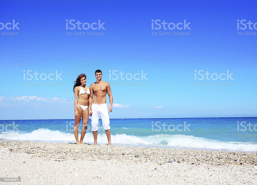 Beautiful couple stands and looks at the camera on beach. stock photo