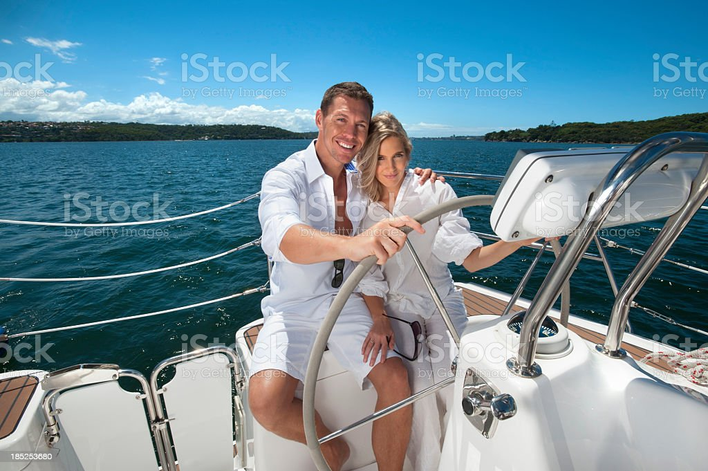 Beautiful couple steering sailing boat royalty-free stock photo