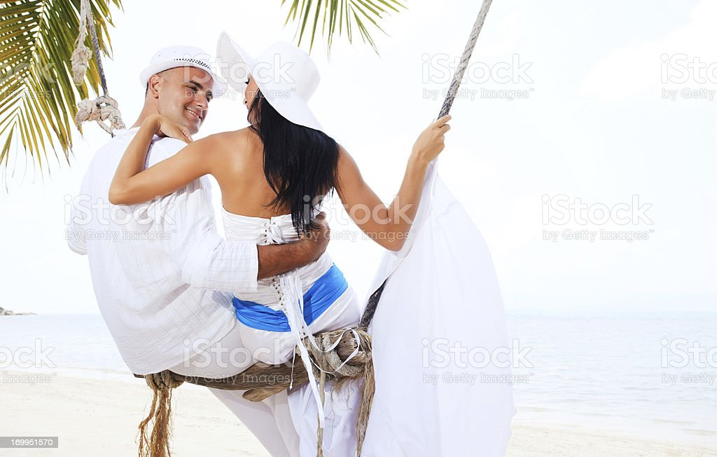 Beautiful couple swinging on the beach royalty-free stock photo