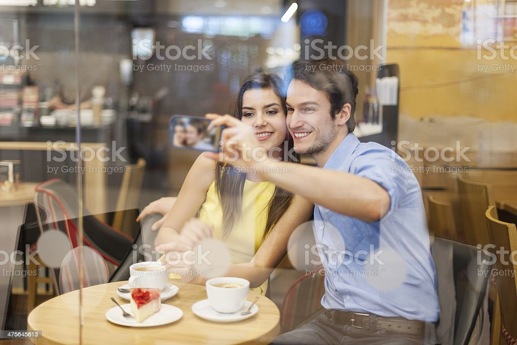 Beautiful couple taking selfie photo in cafe royalty-free stock photo