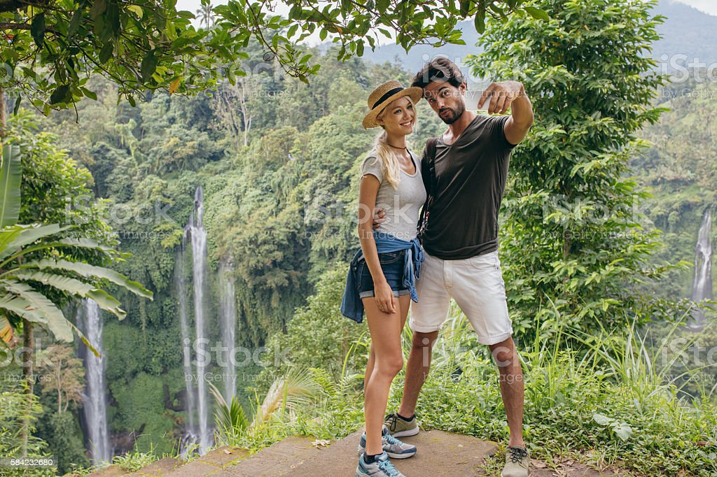 Beautiful couple together on cliff taking selfie with waterfall stock photo