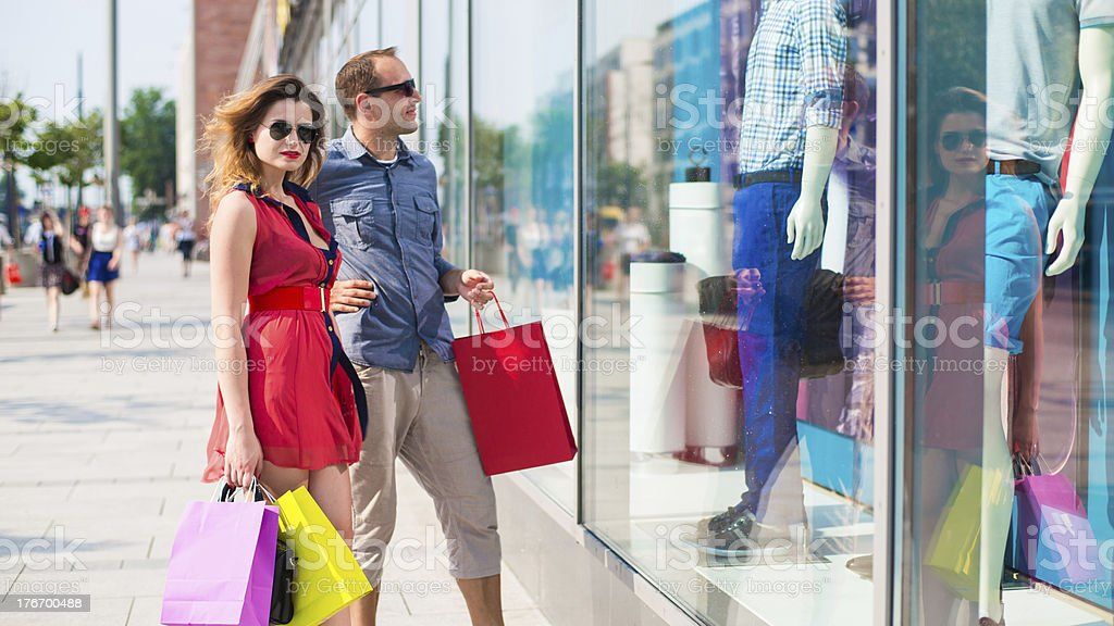 Beautiful couple walking through the mall carrying shopping bags. royalty-free stock photo