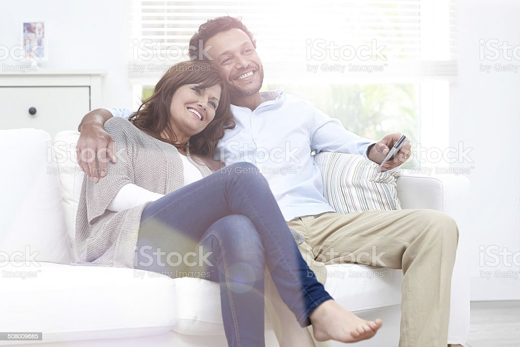 Beautiful couple watching TV at home stock photo