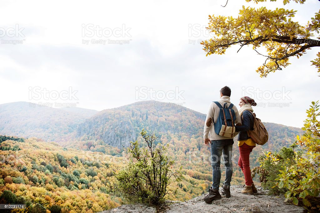 Beautiful couple with backpacks against colorful autumn forest stock photo