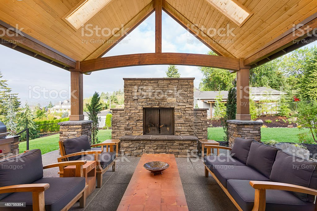 Covered patio with chairs and fireplace