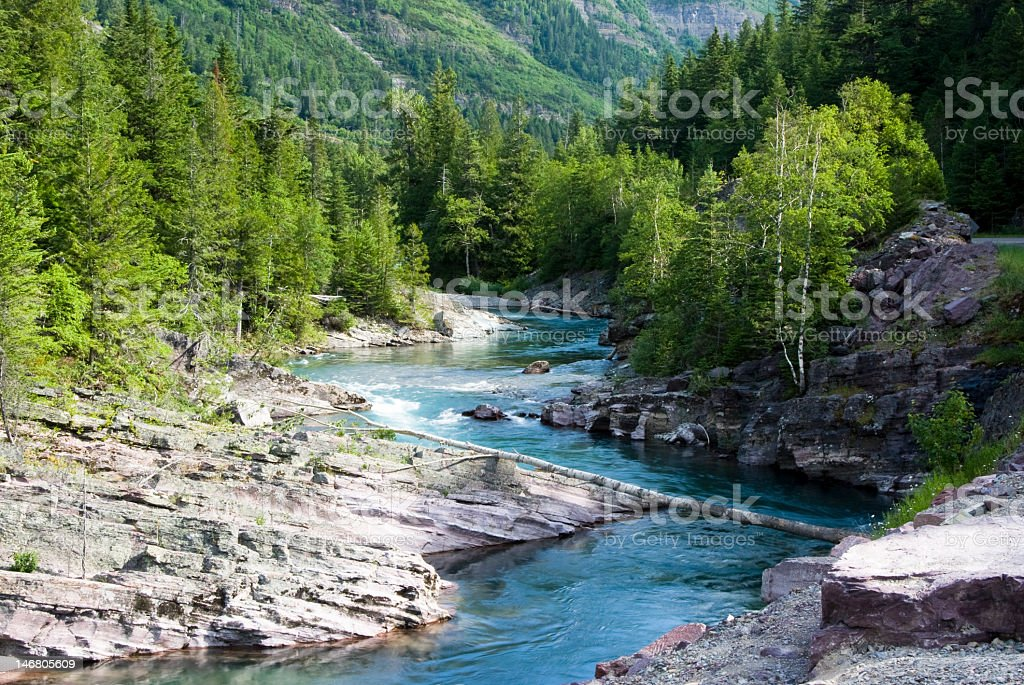 A beautiful creek surrounded by mountains and trees stock photo