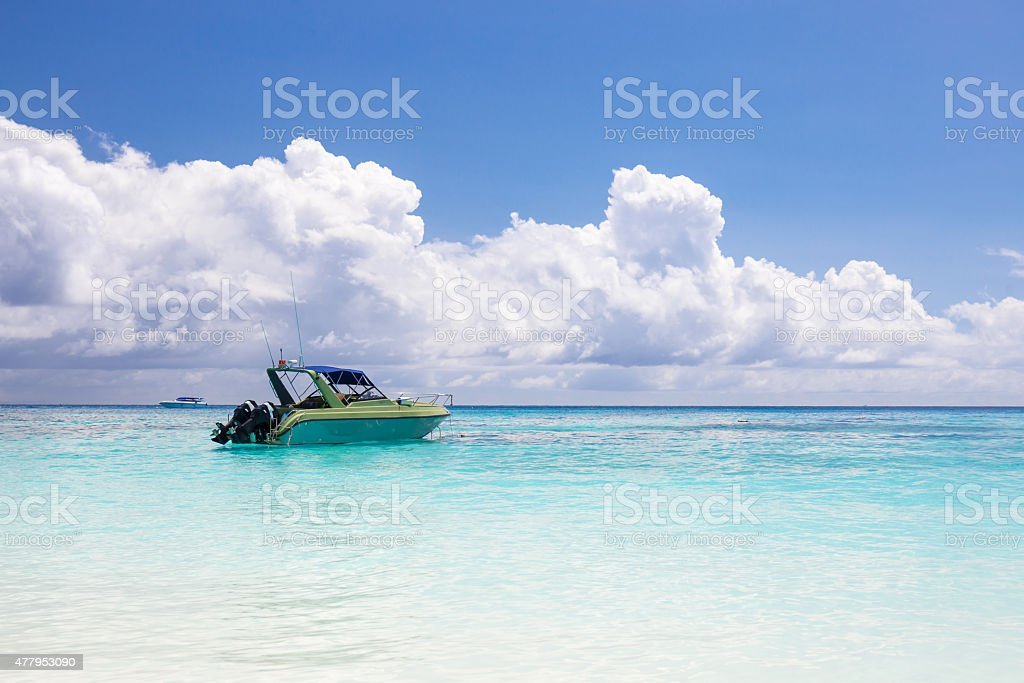 Beautiful crystal clear sea and white sand beach with boat stock photo
