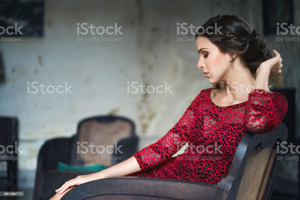 Beautiful cuban woman sitting on armchair at home stock photo