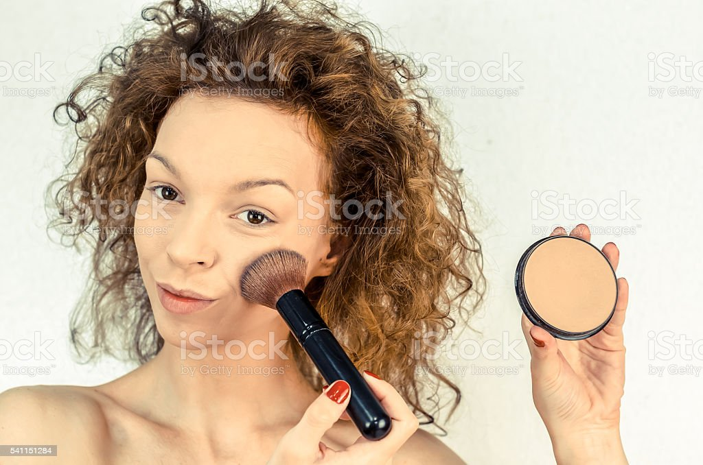 beautiful curly girl applied a powder compact on the cheek stock photo