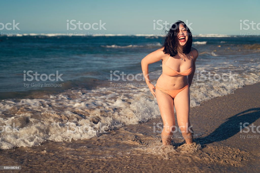 Beautiful curvy young woman enjoying ocean at the beach. stock photo