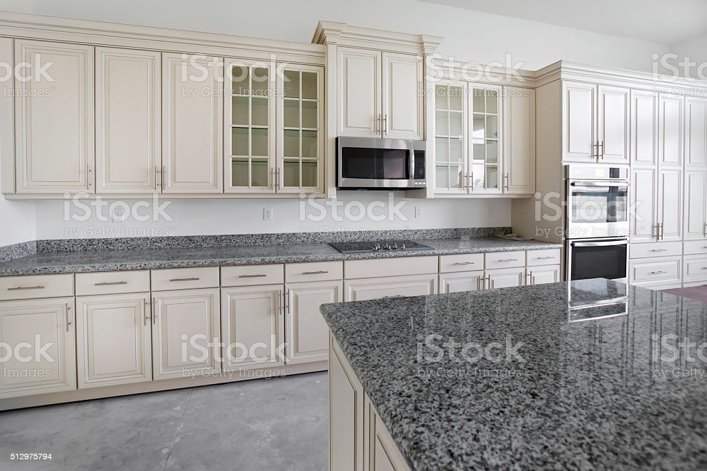 Beautiful custom kitchen in unfinished new home under construction stock photo