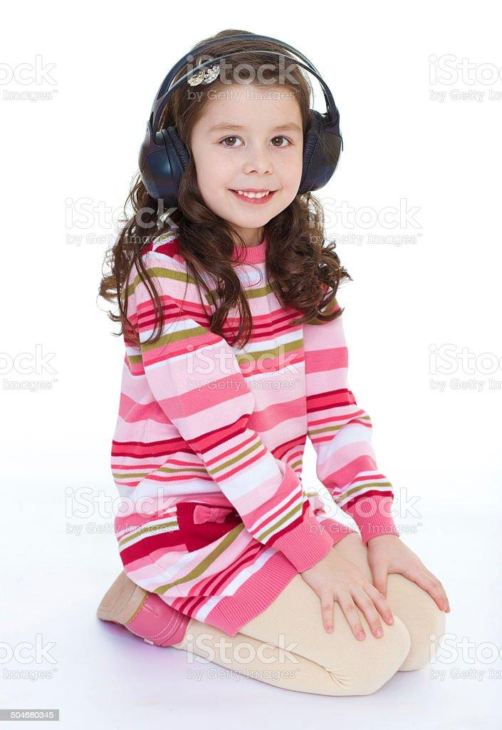 Belle jolie fillette heureuse avec des écouteurs. photo libre de droits