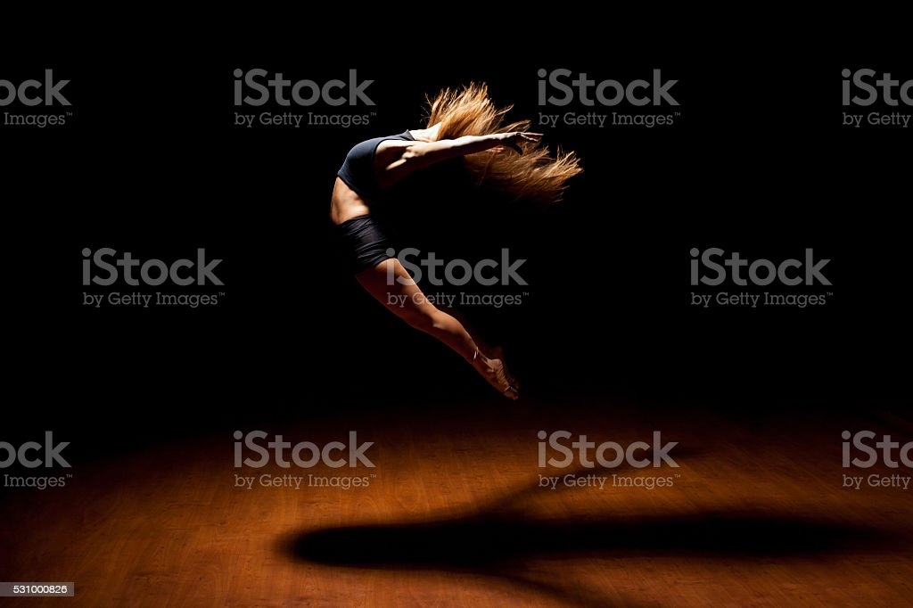 Beautiful dancer jumping in a stage stock photo