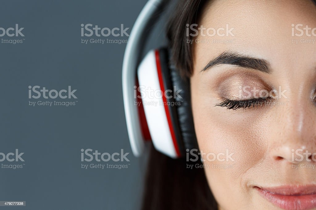 Beautiful dark haired smiling woman wearing headphones stock photo