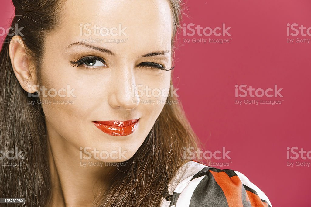 Beautiful dark-haired girl winks stock photo