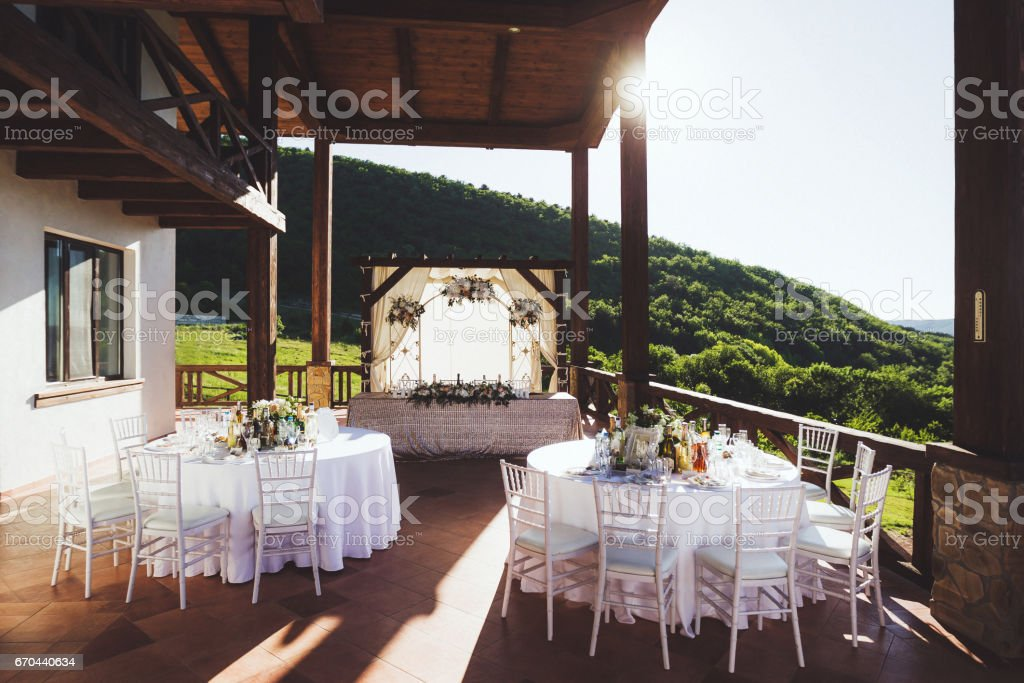 Beautiful decorated wedding ceremony outdoor with mountain view. A lot of white chairs and carved forged arch with flowers stock photo