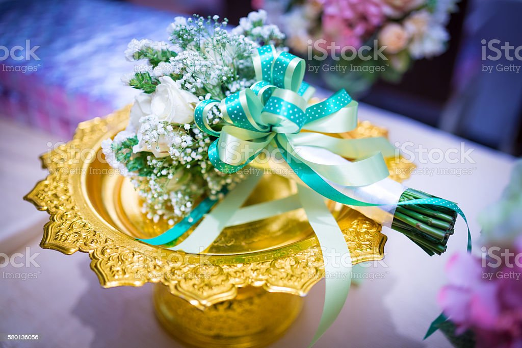 Beautiful delicate bridal bouquet on a gold phan. stock photo