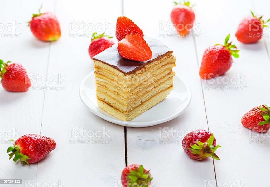 Beautiful delicious homemade cake with strawberries on white wooden table. stock photo