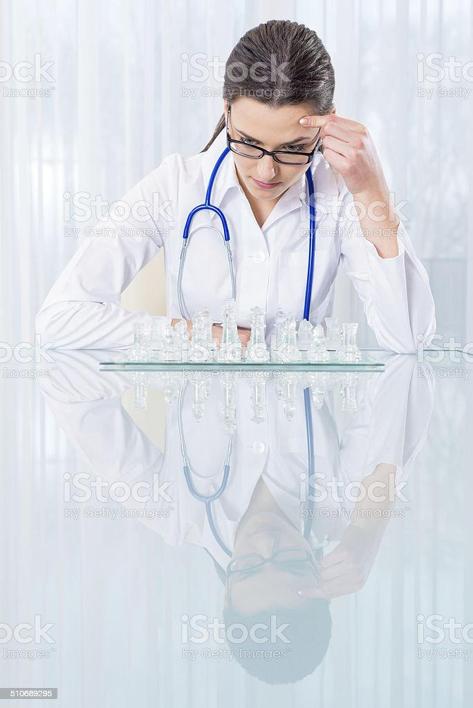 Beautiful doctor playing chess stock photo