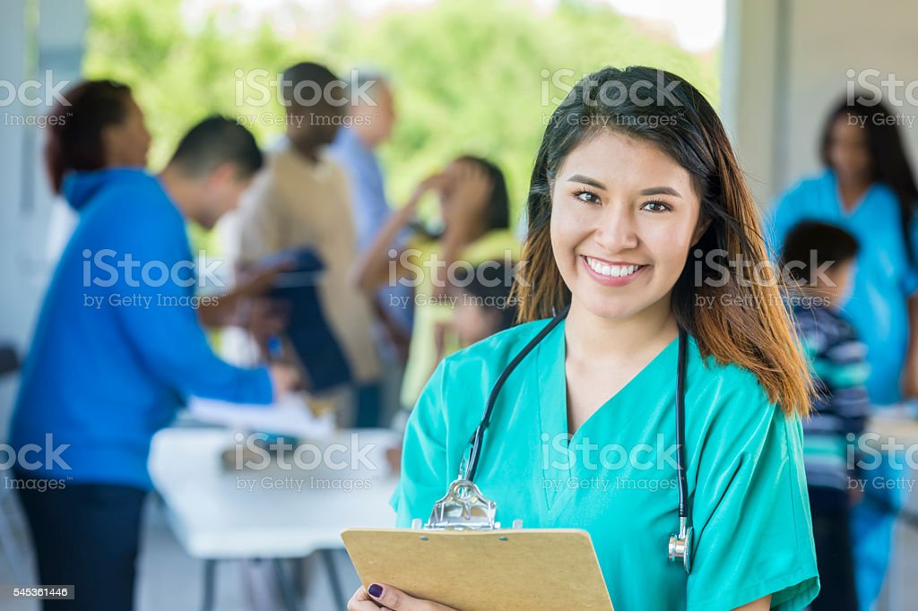 Beautiful doctor smiling at camera holding clipboard stock photo