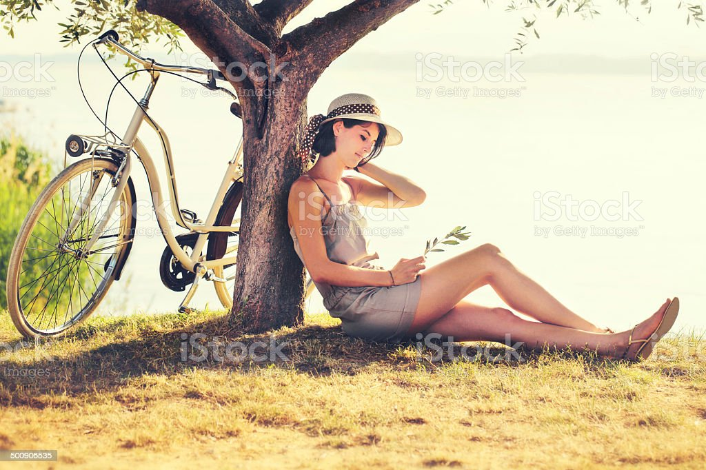 Beautiful dormant woman in love waiting under an olive's tree stock photo