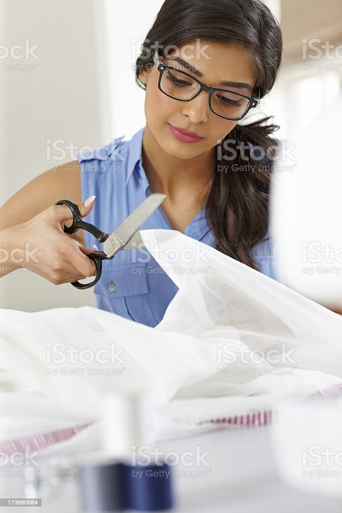 Beautiful dressmaker cutting a piece of white material royalty-free stock photo