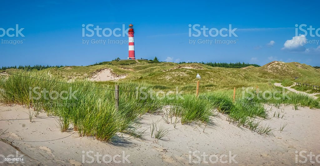 Beautiful dune landscape with traditional lighthouse at North Sea stock photo