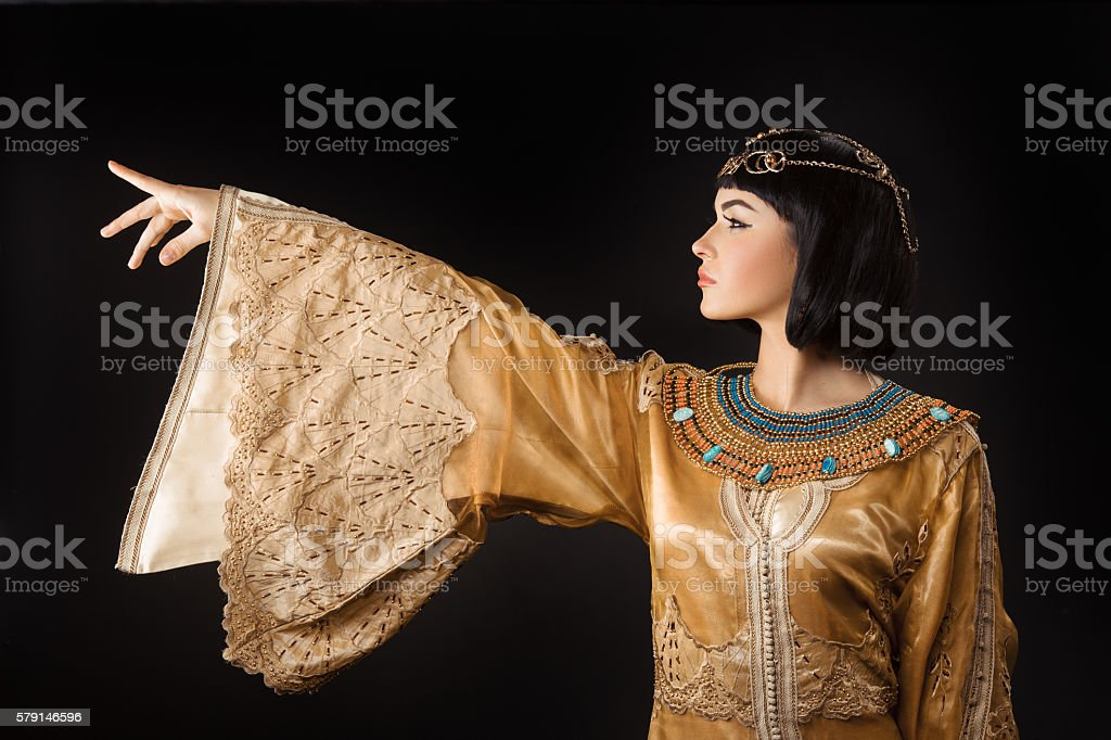 Beautiful Egyptian woman like Cleopatra pointing finger away on black stock photo