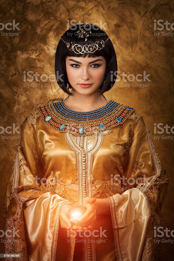 Beautiful Egyptian woman like Cleopatra with magic ball on golden stock photo
