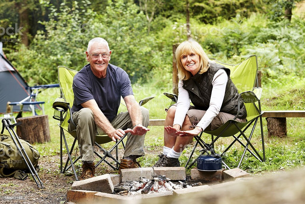 Beautiful elderly couple harming hands on campfire royalty-free stock photo
