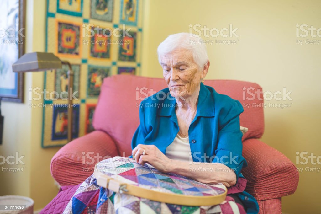 Beautiful elderly woman in apartment crafting stock photo