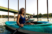 Beautiful elderly woman sitting in her kayak on the river