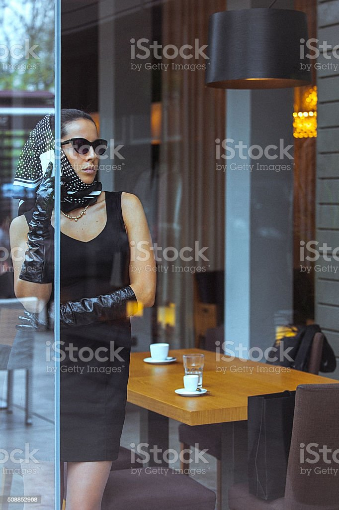 Beautiful, elegant woman talking on the mobile phone at cafe stock photo