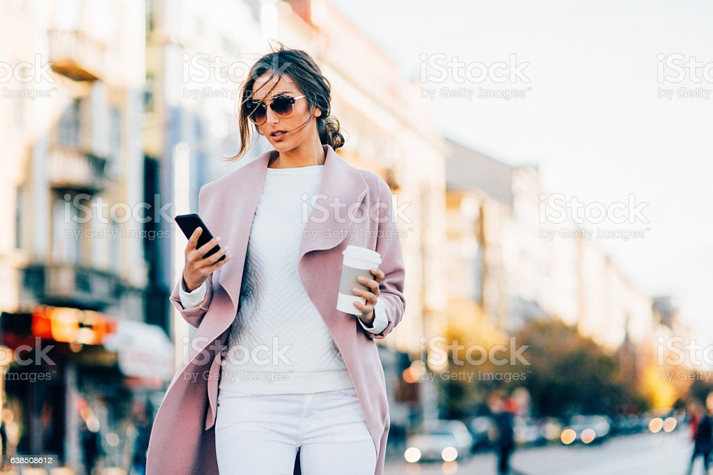 Beautiful elegant woman texting outdoors stock photo